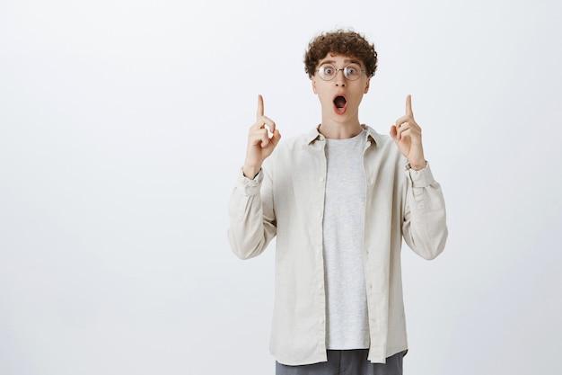 Ragazzo adolescente impressionato felice che posa contro il muro bianco
