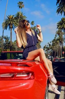 Счастливая впечатлительная девушка с поднятой рукой позирует на красном кабриолете на удивительных пальмах и небе в солнечной калифорнии во время отпуска.