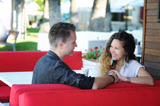 通りのカフェに座って、お互いを見て、屋外で恋に幸せなカップル