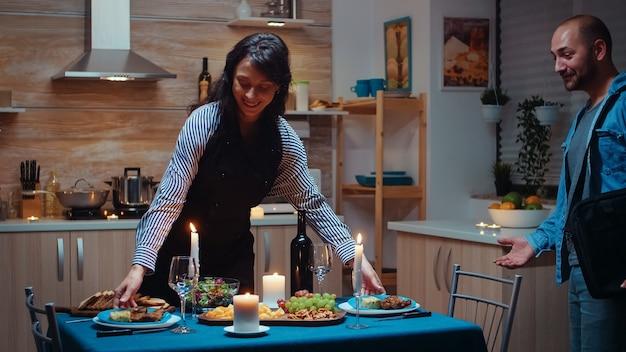 행복하고 사랑에 빠진 여자가 축제 저녁 식사를 준비하고 직장에서 돌아온 남자가 아내에게 키스하고 껴안고 놀랐습니다. 그녀의 남편을 위해 요리를 하는 젊은 백인 여성, 부엌에서 기다리는 낭만적인 저녁 식사.