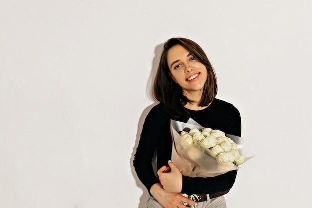 짧은 머리 꽃과 함께 포즈를 취하는 행복 한 놀라운 여자