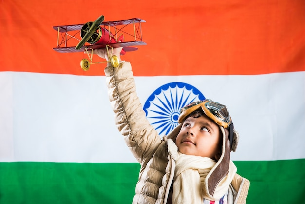 Happy indian or asian boy kid playing with toy metal airplane in world war 2 pilot attire and glasses, standing isolated over indian flag background