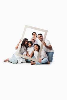 Счастливая индийская азиатская семья из шести поколений, просматривающая пустую рамку, стоя или сидя на белом фоне в белых тканях и синих джинсах