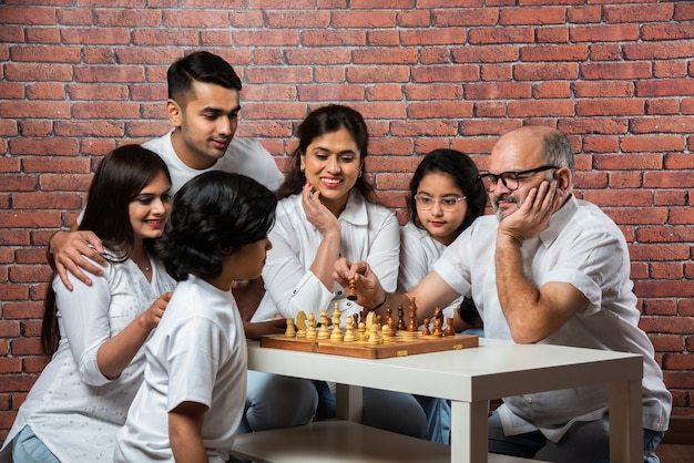 赤レンガの壁に白い布を着て、人気のボードゲームであるチェスまたはshatranjをプレイする6人の幸せなインドのアジアの多世代家族