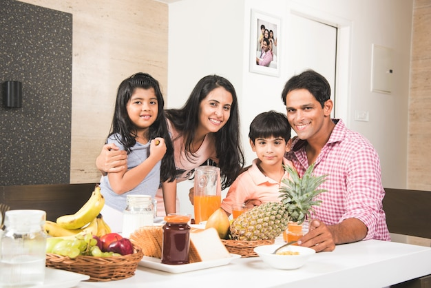 幸せなインドのアジアの若い家族家で食事をし、楽しんでいます。セレクティブフォーカス