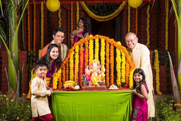 Счастливая индийская семья празднует фестиваль ганеша или чатурти, приветствуя или исполняя пуджу и поедая дома сладости в традиционной одежде, украшенной цветами календулы