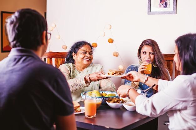 Счастливая индийская семья вместе едят праздничный ужин