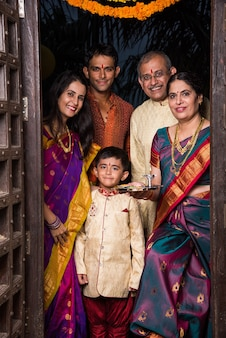 Happy indian family entering house with puja thali through old antique door - griha pravesh or gruha pravesh