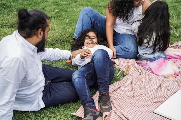 행복한 인도 가족은 도시 공원에서 즐겁게 그림을 그리고 함께 웃고 - 소년 얼굴에 초점