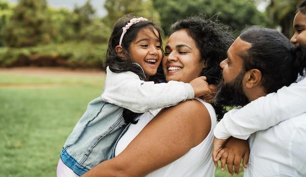 屋外で楽しんで幸せなインドの家族