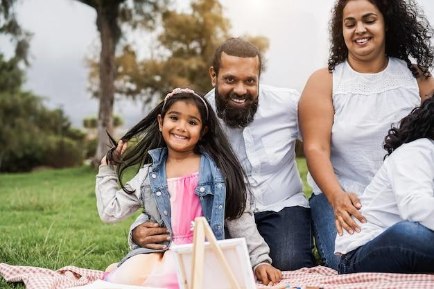 Счастливая индийская семья весело рисует с детьми на открытом воздухе в городском парке - основное внимание уделяется лицу девушки
