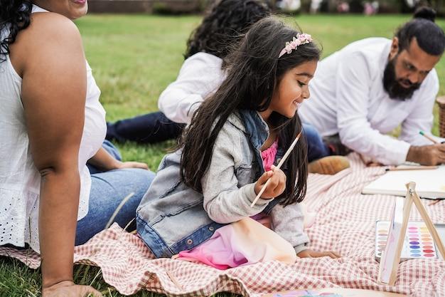 행복한 인도 가족이 도시 공원에서 야외에서 아이들과 즐겁게 그림을 그리고 있습니다 - 소녀의 얼굴에 중점을 둡니다