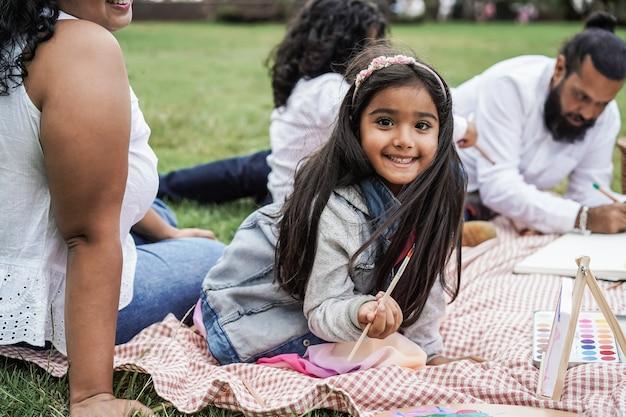 都市公園で屋外の子供たちと一緒に絵を描くのを楽しんでいる幸せなインドの家族-主な小さな女の子の顔
