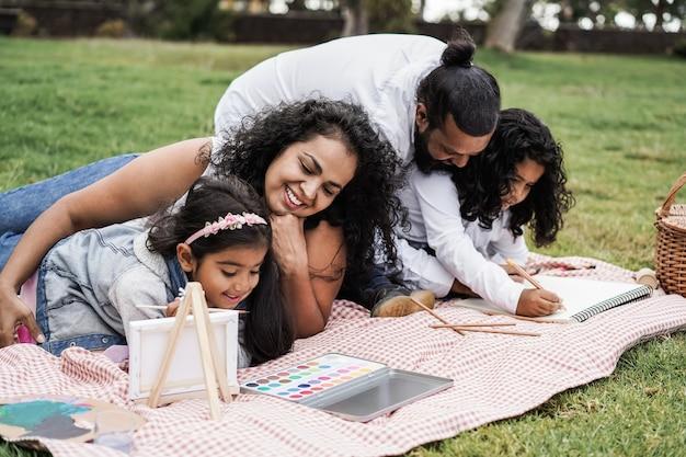 都市公園で屋外の子供たちと一緒に絵を描くことを楽しんでいる幸せなインドの家族