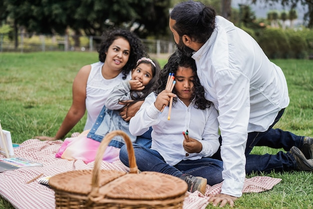 Happy indian family having fun painting with children outdoor at city park - main focus on girl face
