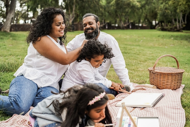 Happy indian family having fun painting with children outdoor at city park