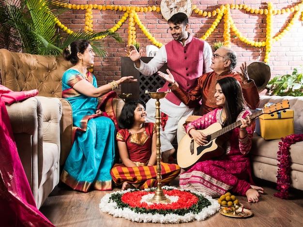 전통적인 옷으로 축제를 축하하면서 행복한 인도 가족 노래, 음악 연주, 기타