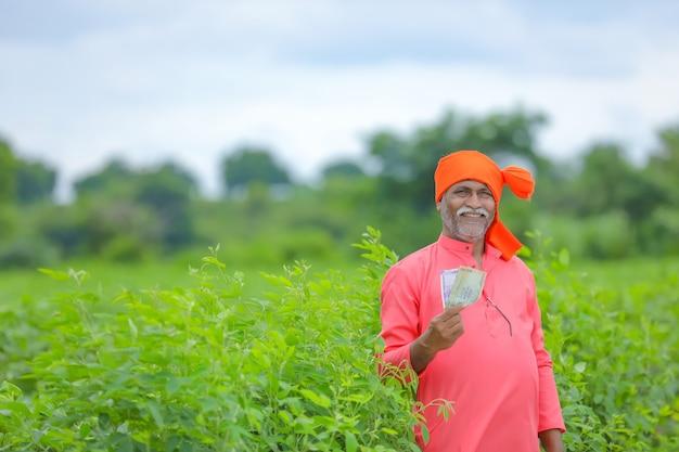 Счастливый индийский фермер, показывая индийские рупии на поле