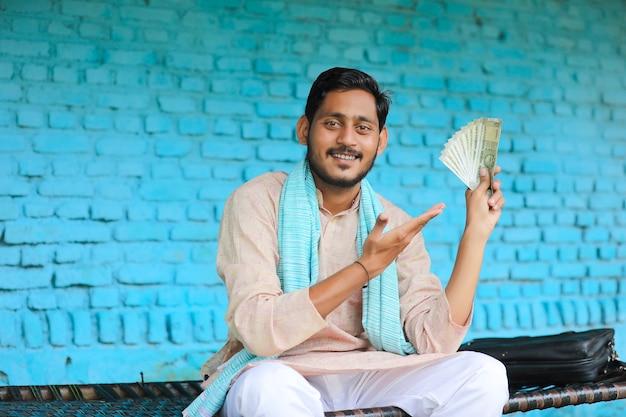 家でお金を見せて幸せなインドの農夫。
