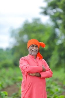 Happy indian farmer standing and smile at field