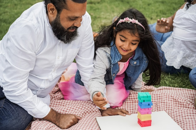 Счастливый индийский отец и ребенок девочка весело играя на открытом воздухе в городском парке