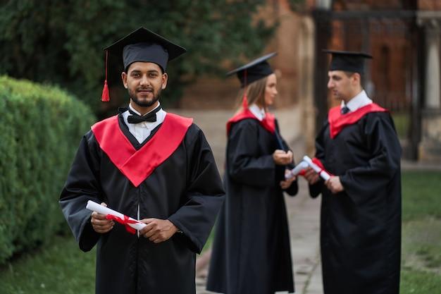 卒業ローブの幸せなインドの卒業生は、キャンパスで卒業証書を保持しています。