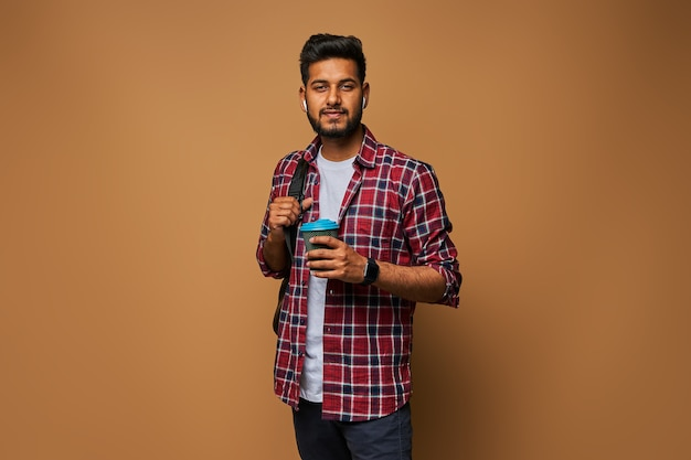 Happy indian man in casual clothes with coffee to go and backpack on pastel wall