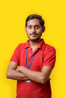 Tシャツを着て、黄色の背景に分離された表情を示す幸せなインド人。