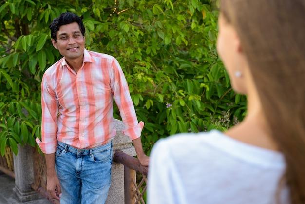 笑みを浮かべて、愛の美しい女性を見て幸せなインド人