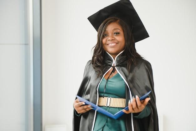 Счастливый индийский студент университета в выпускном платье и кепке с дипломом. портрет смешанной расы азиатских индейцев и африканцев. Premium Фотографии