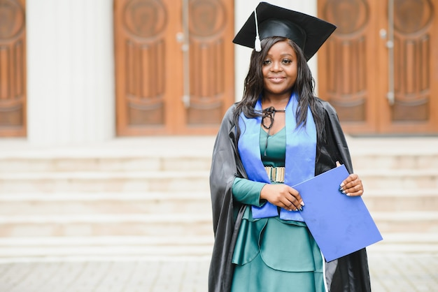 Счастливый индийский студент университета в выпускном платье и кепке с дипломом. портрет смешанной расы азиатских индейцев и африканцев.
