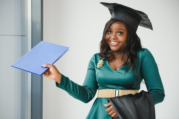 Счастливый студент индийского университета в выпускном платье и кепке.
