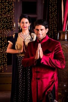 Namaskara 또는 손에 행복 인도 젊은 커플 접힌 디 왈리 축제에 포즈, 손님 환영