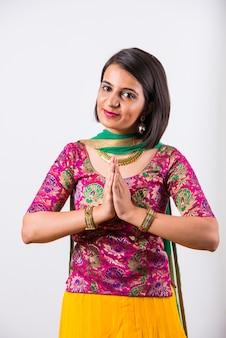 ナマステまたは歓迎のポーズで民族レヘンガの幸せなインドの若い女の子、白い背景で隔離。