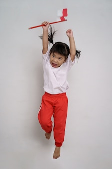 Счастливый индонезийский ребенок с флагом