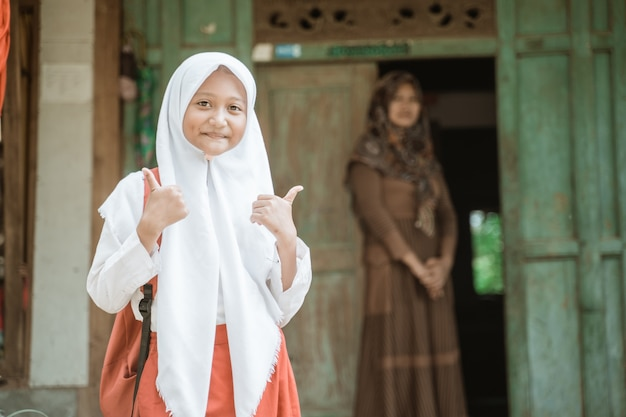 Happy indonesian student getting ready to school in the morning standing in front of her house