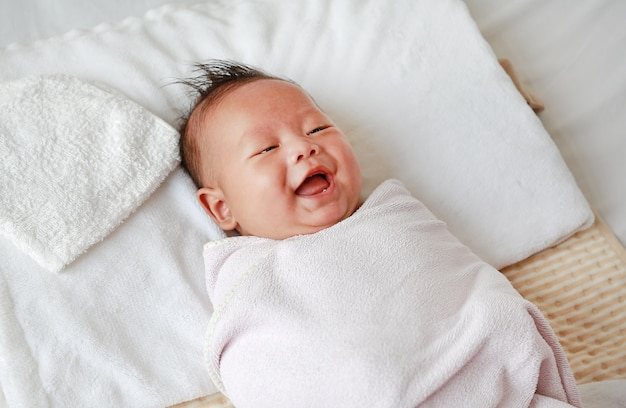 Happy infant baby boy in towel roll lying on bed after bath.