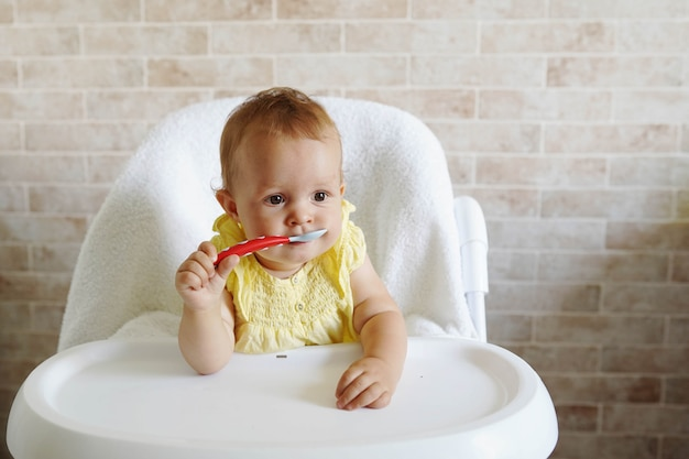 Happy infant baby girl spoon eats itself at home