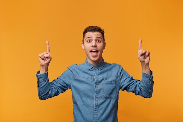 Happy inspired guy shows with his index fingers on the empty space above his head