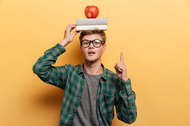 Happy inspired young man with book and apple on his head pointing up and having idea over yellow background