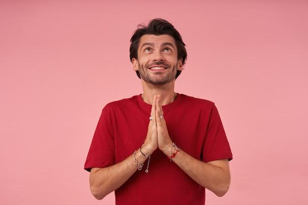 空を見上げて祈る赤いtシャツの剛毛を持つ幸せなインスピレーションを得た若い男