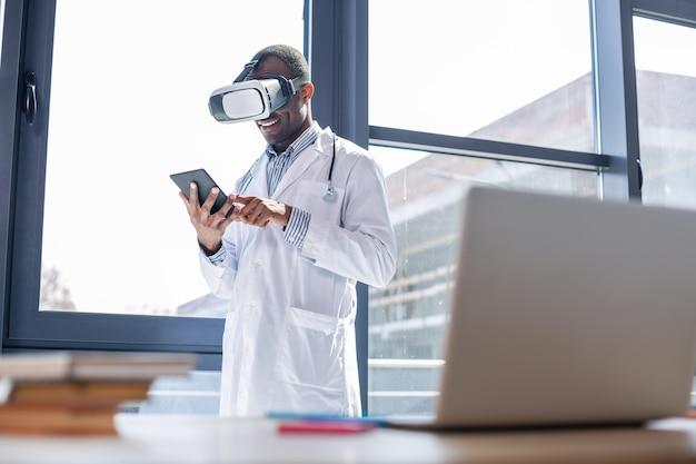Счастливая международная брюнетка склоняет голову во время использования своего гаджета в очках виртуальной реальности