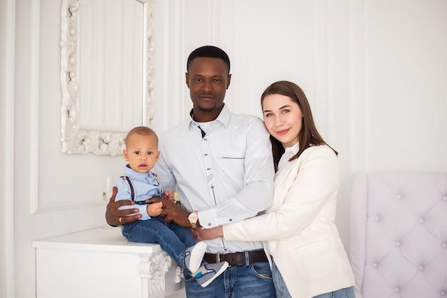 幼い息子と幸せな国際的な若い家族。多民族の両親は、異人種間の男の子の子供と一緒に家でリラックスします。