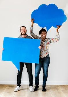Happy interracial couple holding copyspace speech bubble