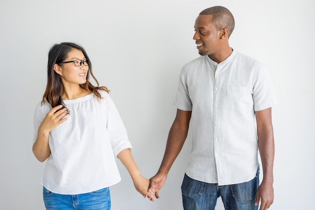 Happy interracial couple holding hands and looking at each other in studio.