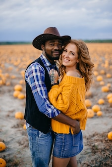 Happy interracial couple in love stands in a pumpkin field