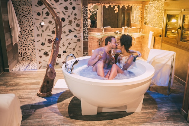 Happy interracial couple relaxed in the jacuzzi enjoying their self and drinking wine