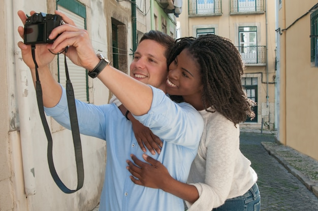 Happy interracial couple taking selfie photo in street