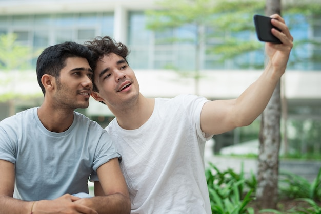 Happy interracial gays posing for cute selfie in city