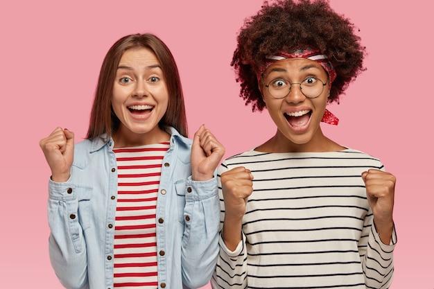 Le felici donne interrazziali si rallegrano con allegria, stringono i pugni, esprimono felicità e trionfo, vincono il primo posto alla competizione